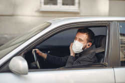 Man driving while wearing a mask
